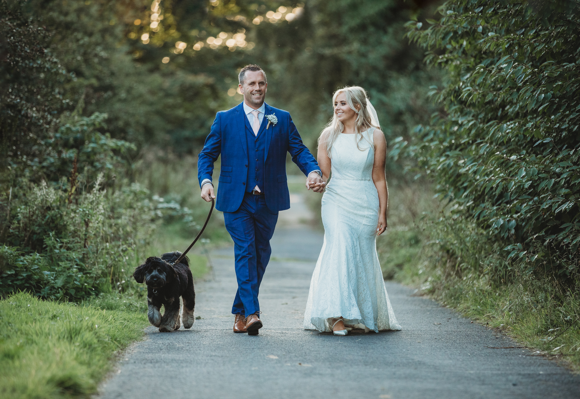 relaxed wedding photography, bridal couple walking with dog